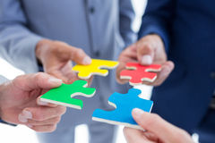 Business colleagues holding piece of puzzle. In the office stock photo