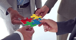 Business colleagues holding pieces of puzzle