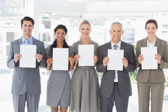 Business colleagues holding sheets of paper together Royalty Free Stock Images