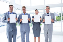 Business colleagues holding sheets of paper together Stock Photo