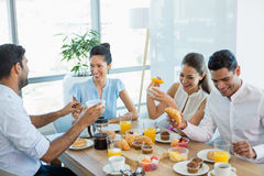 Business colleagues interacting with each other while having breakfast Stock Photography