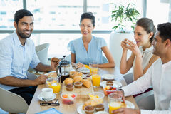 Business colleagues interacting with each other while having breakfast Stock Image