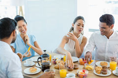 Business colleagues interacting with each other while having breakfast Stock Images