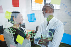 Business colleagues interacting with each other while writing on sticky note. In office Stock Image