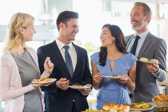 Business colleagues interacting while serving themselves at buffet lunch Stock Image
