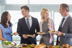 Business colleagues interacting while serving themselves at buffet lunch Stock Photos
