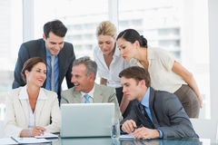 Business colleagues with laptop at desk Stock Photo