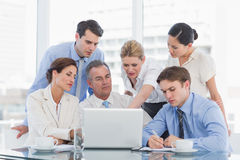 Business colleagues with laptop at desk Royalty Free Stock Image