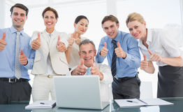 Business colleagues with laptop gesturing thumbs up at desk Royalty Free Stock Images