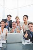 Business colleagues with laptop gesturing thumbs up at desk Royalty Free Stock Image