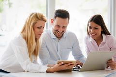 Business colleagues laughing. While looking at the laptop royalty free stock images