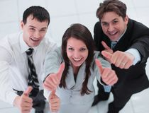 Business colleagues looking at camera and shoving thumbs up in t Royalty Free Stock Image