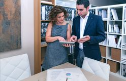 Business colleagues looking documents in electronic devices stock images