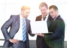 Business colleagues looking at a laptop, standing in the lobby of the office. Stock Images