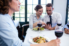 Business colleagues looking at mobile phone during business lunch meeting Royalty Free Stock Images
