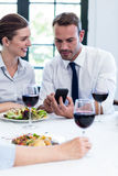 Business colleagues looking at mobile phone during business lunch meeting Royalty Free Stock Photos