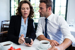 Business colleagues looking at mobile phone while having a meeting Stock Images
