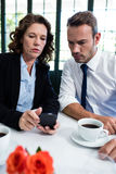 Business colleagues looking at mobile phone while having a meeting Royalty Free Stock Photography