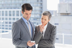 Business colleagues looking at mobile phone Stock Image