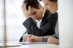 Business colleagues, man and woman, working at office desk Stock Photos