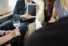 Business Colleagues Meeting In Private Jet Stock Photo