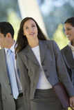 Business colleagues on the move, focus on businesswoman, smiling, portrait (tilt) Stock Photos
