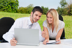 Business colleagues in nature with laptop smile Stock Images