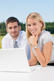 Business colleagues in nature with laptop smile Royalty Free Stock Photography
