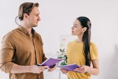 Business colleagues with notebooks having conversation after business training. In office royalty free stock photos
