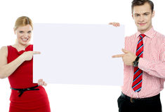 Business colleagues pointing at blank signboard Royalty Free Stock Images