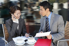 Business Colleagues Reviewing Documents At Outdoor Café Stock Photo