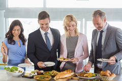 Business colleagues serving themselves at buffet lunch Stock Photo