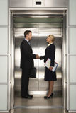 Business Colleagues Shaking Hands In Elevator Royalty Free Stock Photo