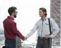 Business colleagues shaking hands at office. Photo with copy space stock photography