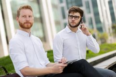 Business colleagues sitting on bench outdoors royalty free stock images