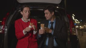 Business colleagues sharing meal in car at night stock footage