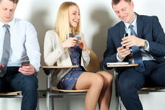Business colleagues sitting on chairs and using  mobile phone. Businesswoman laughing Royalty Free Stock Photo