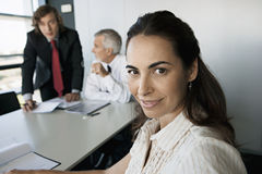 Business colleagues sitting at conference table in meeting room, focus on woman in foreground. Business colleagues sitting at conference table in meeting room Royalty Free Stock Image