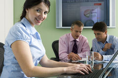 Business colleagues sitting at conference table in meeting room, focus on woman using laptop Stock Photography