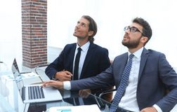 Business colleagues sitting at Desk and looking up. Concept development Stock Photos