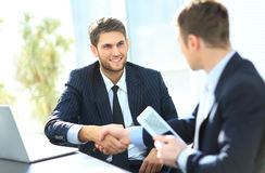 Business colleagues. Sitting at a table during a meeting with two male executives shaking hands stock photography