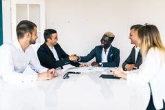 Business colleagues sitting at a table during a meeting with two male executives shaking hands. Team work stock photo