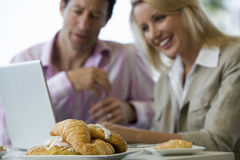 Business colleagues sitting at table, using laptop, smiling, focus on croissants in foreground Stock Image