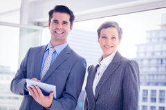 Business colleagues smiling at camera and holding tablet. In the office royalty free stock image