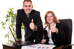 Business colleagues smiling with thumbs up. Satisfied young business colleagues smiling with thumbs up royalty free stock photo