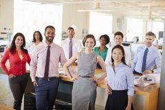Business colleagues smiling to camera in an open plan office royalty free stock photo