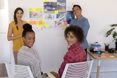 Business colleagues smiling together in office. Portrait of diverse casually dressed business colleagues smiling together in office royalty free stock images