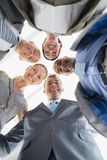 Business colleagues standing in circle and looking at camera Royalty Free Stock Images