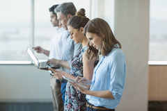 Business colleagues standing in a row using mobile phone, digital tablet and laptop Stock Images