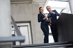 Business colleagues standing on a staircase and talking to each other Stock Photo